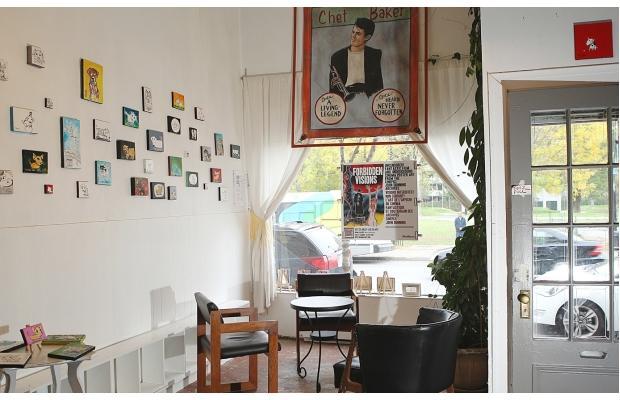 foto interna de um café com mesa e cadeira contra a janela